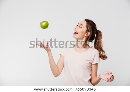 Portrait of a smiling happy girl throwing apple in the air isolated over white background