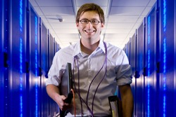 Portrait of a smiling IT technician with laptop and LAN cables standing in the middle of a network server room