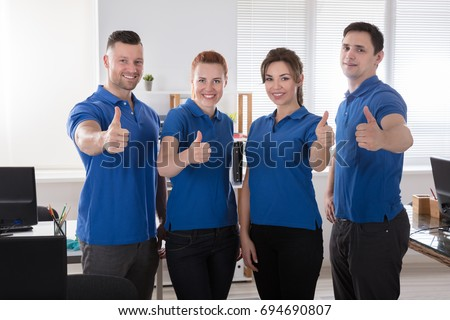 Portrait Of A Smiling Janitors Showing Thumb Up Sign In The Office