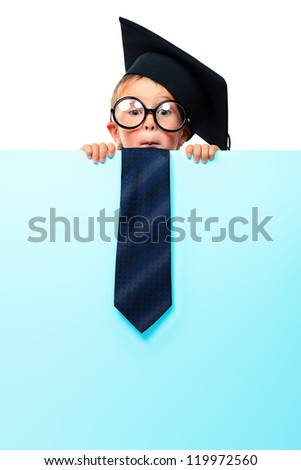 Portrait of a smiling little boy in academic hat and big spectacles holding white board. Isolated over white background.