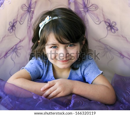 Portrait of a smiling little girl in blue and purple