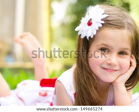 Stock Photo Portrait of a smiling little girl lying on green grass