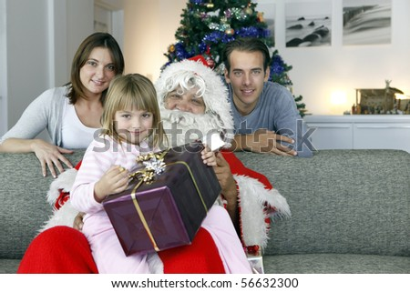 Portrait of a smiling little girl sitting on Santa Claus with a gift in the hands