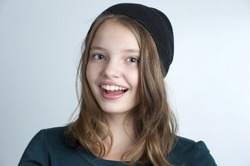 Portrait of a smiling little girl. Studio photography on a light gray background. Age of child 10 years.