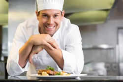 Portrait of a smiling male chef with cooked food standing in the kitchen
