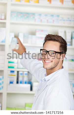 Portrait of a smiling male pharmacist with drug package in front of medicines at drugstore