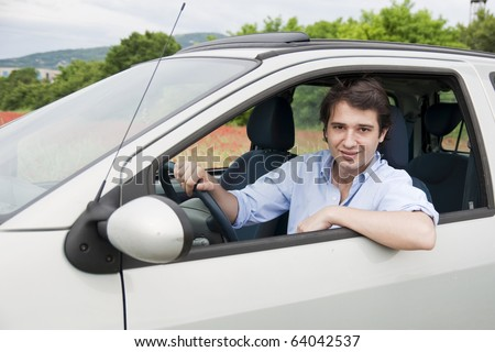 portrait of a smiling man driving his car
