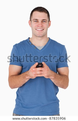 Portrait of a smiling man holding his mobile phone against a white background