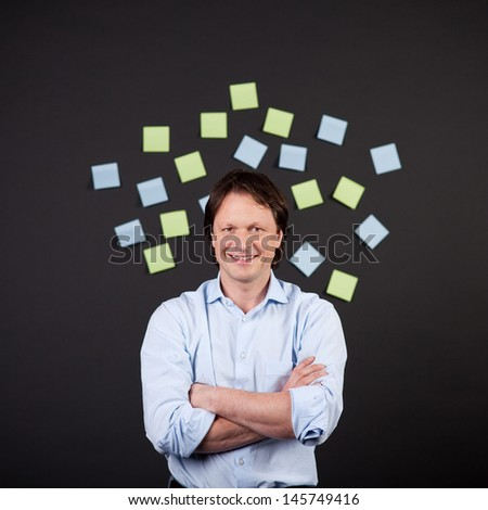 portrait of a smiling man in the middle of paper notes
