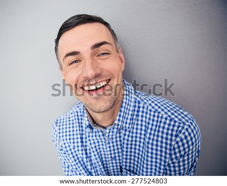 Portrait of a smiling man looking at camera over gray background - Shutterstock ID 277524803