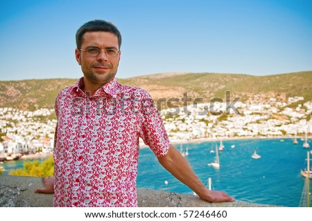 portrait of a smiling man standing in front of the sea bay