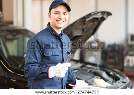 Portrait of a smiling mechanic holding a wrench in his garage