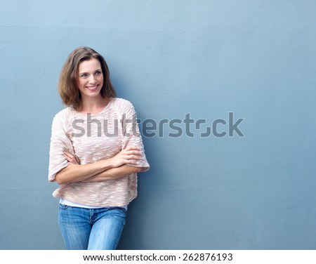 Portrait of a smiling mid adult woman standing with arms crossed on blue background