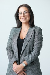 Portrait of a smiling mid-aged business woman (30-35 years old) with dark hair and brown eyes in glasses for vision and a jacket against a light wall. Close-up portrait of a businesswoman.