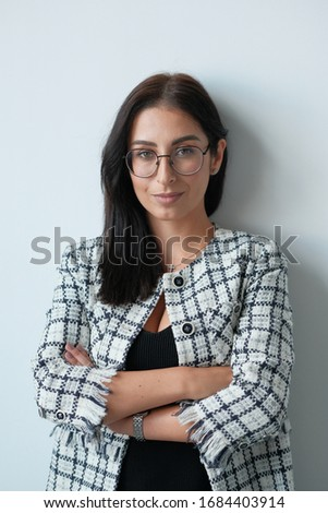 Portrait of a smiling mid-aged business woman (30-35 years old) with dark hair and brown eyes in glasses for vision and a jacket against a light wall. Close-up portrait of a businesswoman. Сток-фото ©