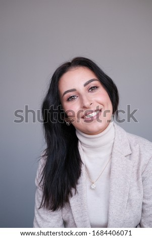 Portrait of a smiling mid-aged business woman (30-35 years old) with dark hair and brown eyes in a milk-colored trouser suit and turtleneck against a light wall. Close-up portrait of a businesswoman Сток-фото ©