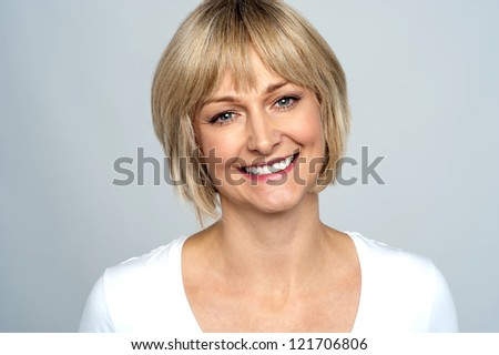 Portrait of a smiling middle aged caucasian woman isolated against grey background.