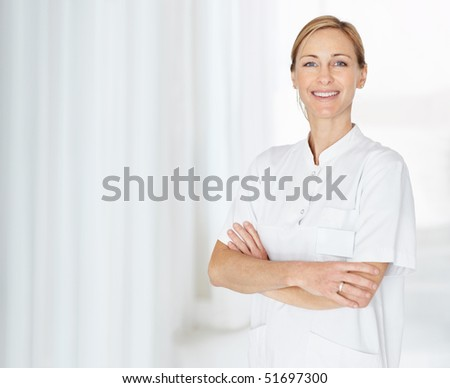 Portrait of a smiling middle aged nurse standing with hands folded