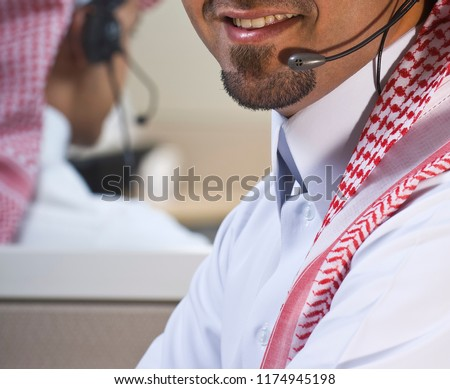 Portrait of a smiling Middle eastern employee with headphones on, in a call center