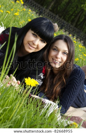 Portrait of a smiling mother and teenage daughter in park