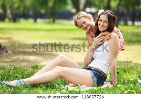 Portrait of a smiling mother and teenage daughter in summer park