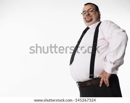 841ee4f388d ... his hip glowering at · Portrait of a smiling overweight businessman  standing with hand on hip against white background  145267324