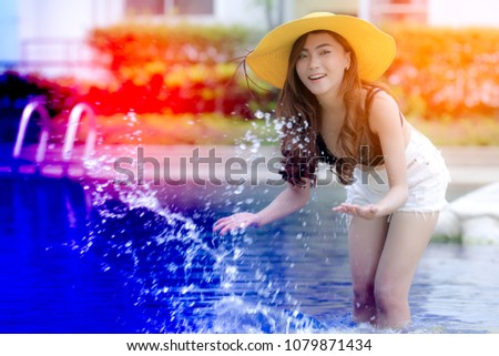 c67060b027941 Portrait of a smiling pretty asian girl in swimsuit with yellow summer hat  on summer vacation
