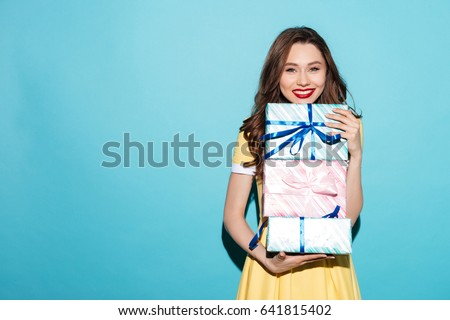 Portrait of a smiling pretty girl holding stack of gift boxes isolated over blue background #641815402