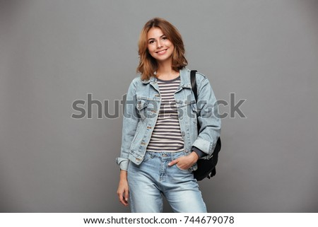 Portrait of a smiling pretty girl in denim jacket holding backpack and looking at camera isolated over gray background