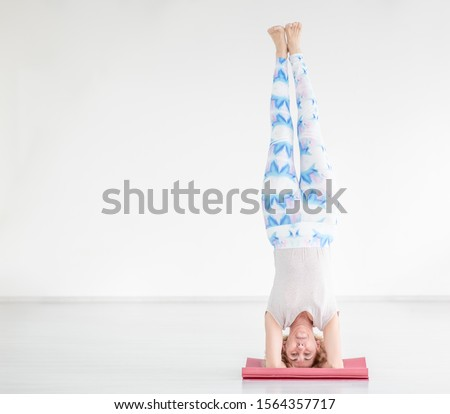 Portrait of a smiling senior woman doing advanced yoga or pilates. Supported headstand, salamba sirsasana. Empty space for text