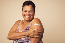 Portrait of a smiling senior woman receiving a vaccine. Mature woman showing her arm with bandage after vaccination.