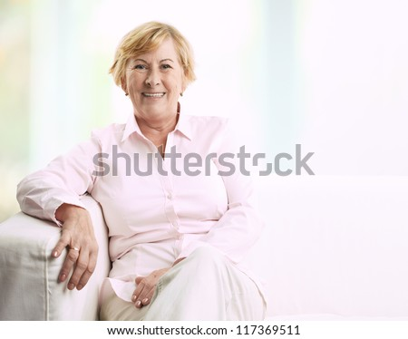 Portrait of a smiling senior woman sitting on couch at home