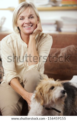 Portrait of a smiling senior woman sitting on couch with her dog