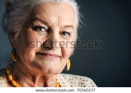 Portrait of a smiling senior woman. Studio shot over grey background.