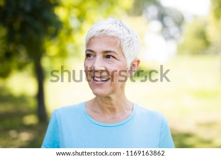 Portrait of a smiling sporty senior woman in a park at summer day #1169163862