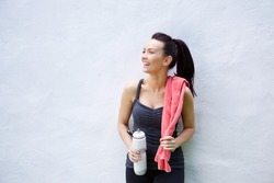Portrait of a smiling sporty woman standing with water bottle and towel