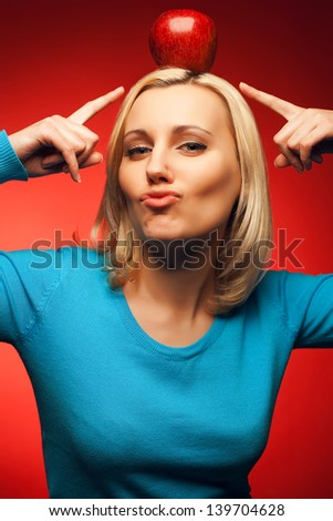Portrait of a smiling student girl posing over red background and pointing to red apple on her head. Education, healthcare (vegetarian) concept. Perfect blond hair, natural make-up. Hipster style.