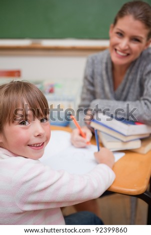 Portrait of a smiling teacher explaining something to her pupil in a classroom
