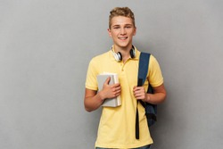 Portrait of a smiling teenage boy with headphones holding books and carrying backpack over gray background
