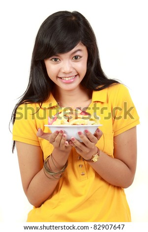 portrait of a smiling teenage girl holding a bowl of cut fruits against white