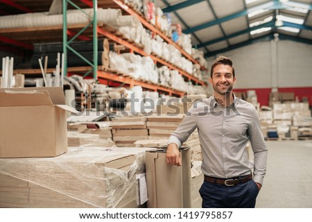Portrait of a smiling warehouse manager leaning against some stock with piles of carpets stacked on shelves in the background ストックフォト ©