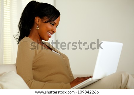 Portrait of a smiling woman browsing the Internet on her laptop while sitting on sofa at home