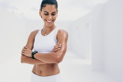 Portrait of a smiling woman in fitness wear relaxing standing with arms crossed. Portrait of a fitness woman in cheerful mood taking a break from workout.
