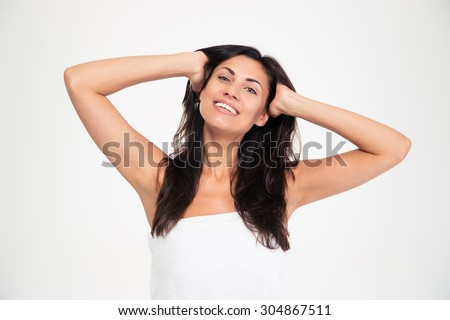 Portrait of a smiling woman in towel touching her hair and looking at camera isolated on a white background #304867511
