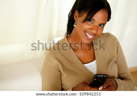 Portrait of a smiling woman looking at you while sending a message with her cellphone