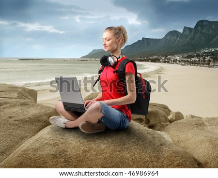 Portrait of a smiling woman sitting on a rock at the seaside and using a laptop