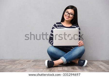Portrait of a smiling woman sitting on the floor with laptop computer on gray background #331294697