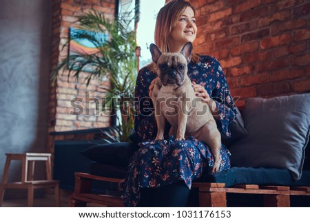 Portrait of a smiling woman sitting with a cute pug in a room wi
