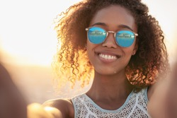 Portrait of a smiling woman wearing sunglasses at the beach