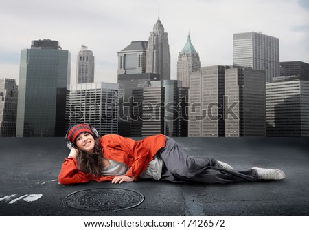 Portrait of a smiling woman with headphones lying in the middle of a city street